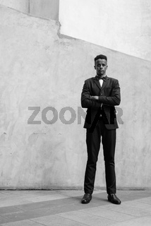 Young handsome African businessman wearing suit against concrete wall outdoors