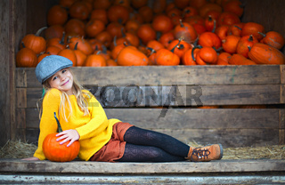 Happy little girl at the autumn pumpkin patch background