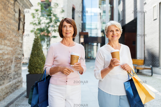 senior women with shopping bags and coffee in city