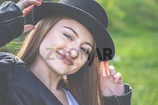 Junge Frau mit Lederjacke und Hut im Garten - Frühling und Sonnenschein im Grünen genießen.
