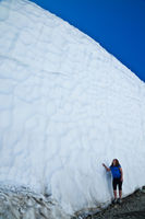 Young woman standing beside a giant snow bank in Whistler, British Columbia