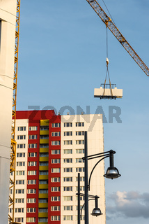 A new building and a skyscraper with a crane with building material