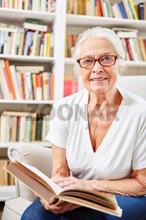 Senior Frau  mit einem Buch in der Bibliothek