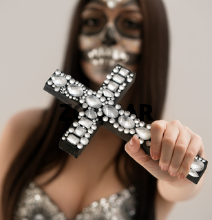 Santa Muerte. Close-up of cross with rhinestones