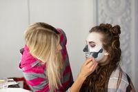 Makeup artist applies body art of a beautiful model