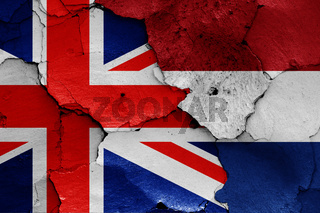 flags of UK and Netherlands painted on cracked wall