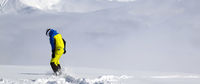 Snowboarder on off-piste slope with new fallen snow