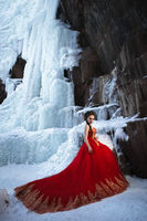 Young beautiful woman in long red dress over winter background