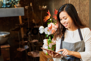 Asiatische Floristin mit Tablet Computer