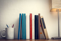 Books with empty board on a wooden desk next to a cup with colored pencils and a lamp