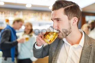 Junger Mann trinkt ein Glas Bier in einem Pub