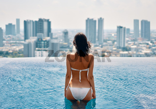 Young beautiful woman relax in swimming pool on rooftop and enjoy cityscape