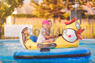 Two young girls playing in a kids' bumper boat