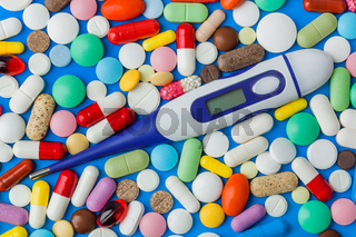 Pills and electronic thermometer with blank screen - medical background
