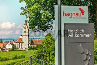 Hagnau, Germany - June 23, 2019: Panoramic view of lake of Lake Constance and the Catholic Church St. Johann Baptist in Hagnau. In the foreground the entry sign of the village Hagnau.
