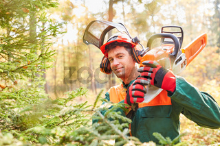 Zufriedener Waldarbeiter mit Motorsäge im Wald