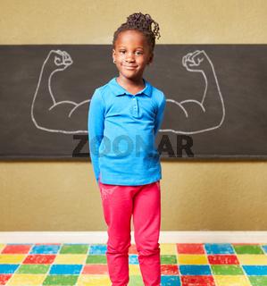 Afrikanisches Mädchen vor Tafel mit Muskeln