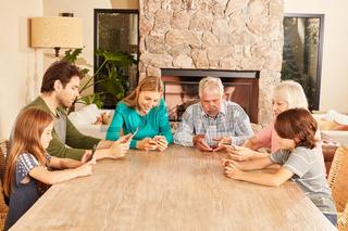 Großfamilie beim Spielen mit Tablet und Smartphone