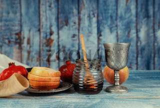 On the table in the synagogue are the symbols of Rosh Hashanah apple and pomegranate, shofar talith