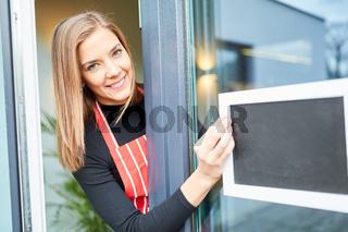 Kellnerin im Restaurant schreibt an leere Tafel