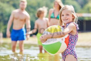 Mädchen spielt mit einem bunten Ball im Meer