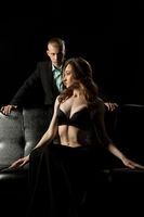 Gorgeous sexy couple on black sofa at night view