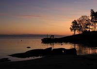 Bright orange morning sky and shore of Lake Vanern, Sweden.