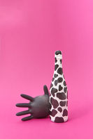 Latex glove balloon with painted white bottle with black spots.