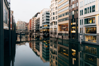 Scenic view of Bleichenfleet canal in Hamburg with luxury fashion stores reflection on water at evening