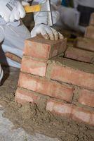 Mason builds brick wall with small bricks and masonry hammer - close-up