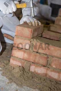 Maurer errichtet Ziegelwand mit kleinen Ziegelsteinen und Maurerhammer - Nahaufnahme