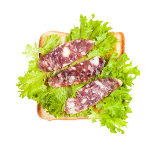 open sandwich with toast, sausage and leaf lettuce