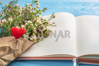 Open notebook and white flower bouquet with a red heart