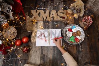 Writing a Christmas list among Christmas decorations and gingerbread