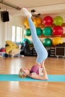 Junge Frau im Yoga Kurs macht eine Kerze