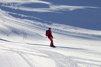 Snowboarder in red downhill on snowy sunlit ski slope