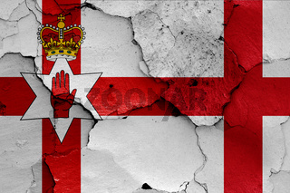 flags of Northern Ireland and England painted on cracked wall
