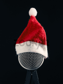 Close up of a microphone with the hat of Santa on a dark studio background