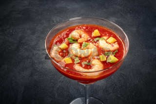 Coctel de gambas, Mexican shrimp cocktail with avocado, close-up on a black background