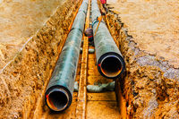 Underground pipe being fixed in trench. Man do a circular welding