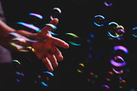 Hand trying to catch colorful bubbles over dark background