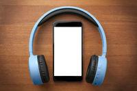 Pair of blue headphones around a blank screen smartphone on orange wooden table