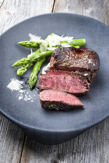 Barbecue dry aged wagyu sirloin beef steak sliced green asparagus and parmesan cheese as closeup on a gray cast iron design plate