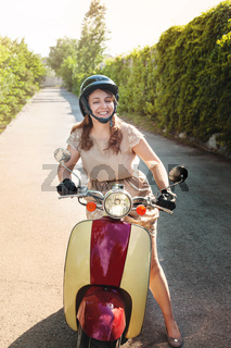 Young woman driving a scooter on a countryside road