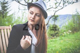 Frühling: elegante junge Frau mit Hut, 20 - 30 Jahre alt, genießt den Sonnenschein im Garten.