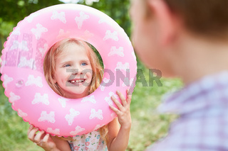 Mädchen spielt mit einem Schwimmring