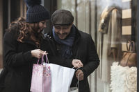 Couple window shopping outdoors in winter