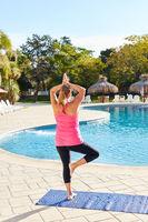 Frau macht Yoga Übung auf einem Bein