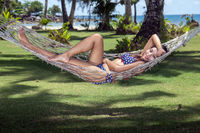Woman is resting in the hammock under the palms