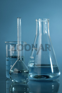 Close up photo of chemical glassware with exam liquids over blue background